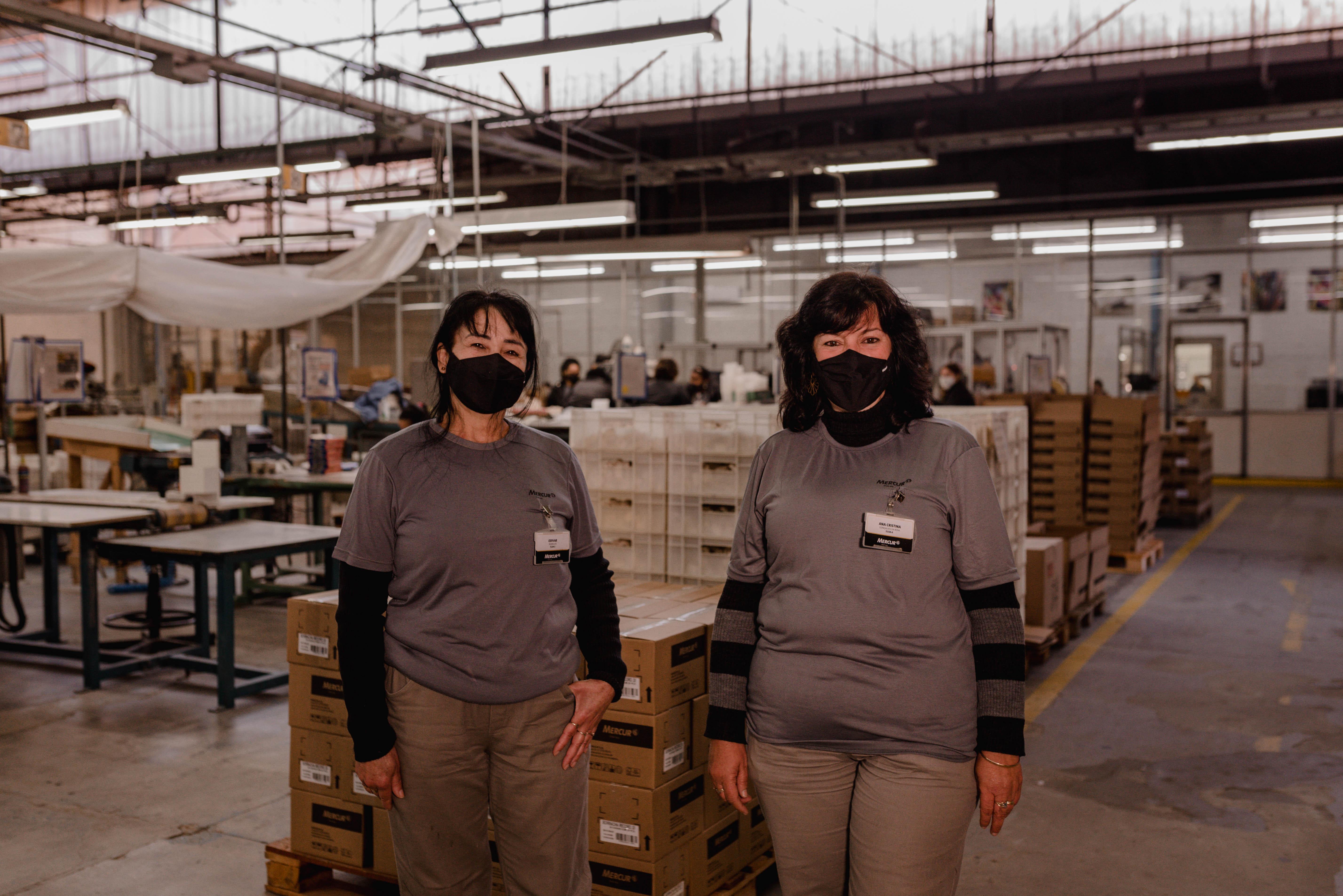 A Odivar e a Ana são colaboradoras da Mercur há 30 e 25 anos, respectivamente, e integram a equipe de produção.<strong>#PraCegoVer</strong> Duas mulheres estão de pé, lado a lado em uma fábrica. Elas usam uniforme cinza e máscaras pretas.