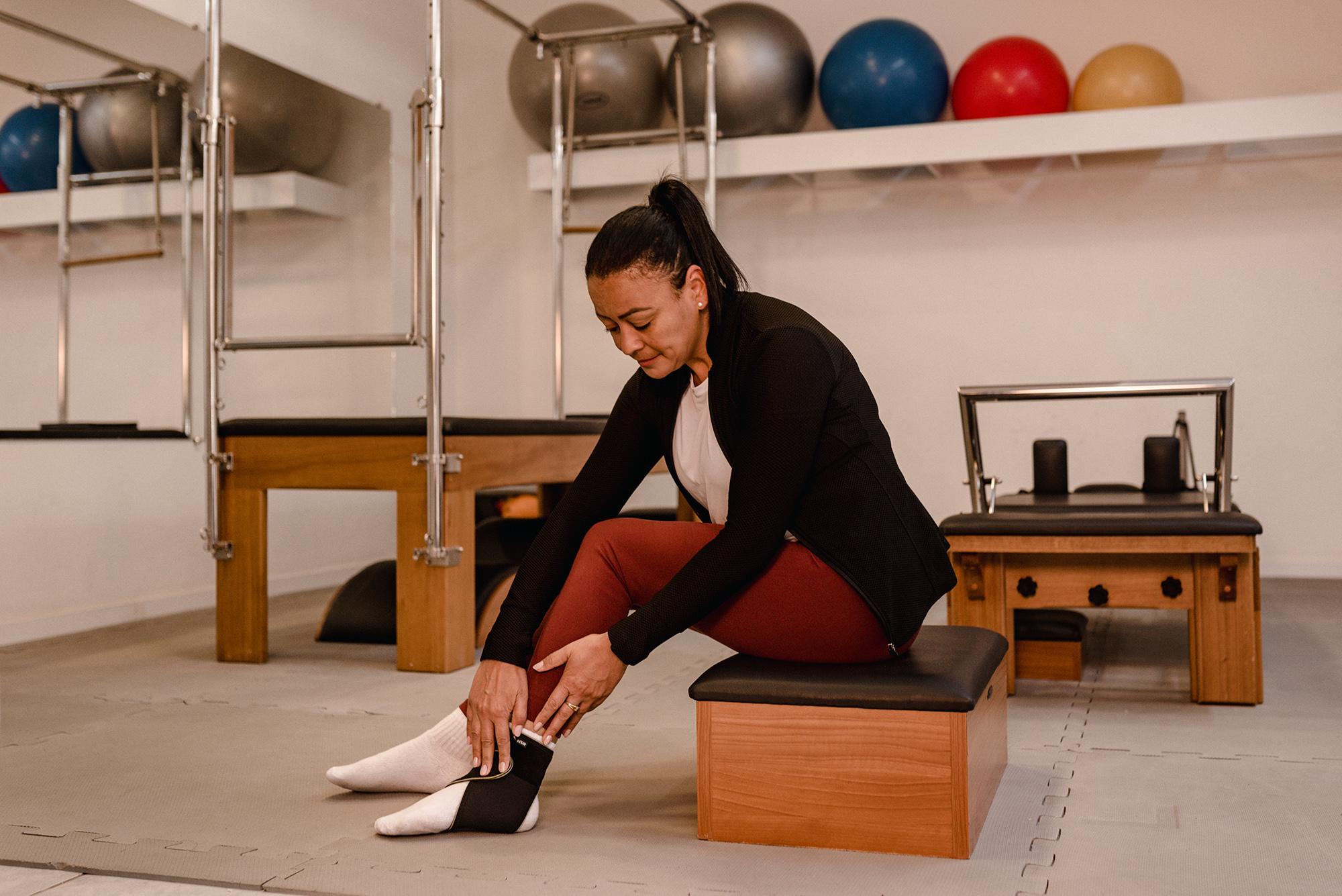 Uma mulher está sentada, vestindo uma tornozeleira em seu pé esquerdo. Ela está em uma sala com equipamentos de pilates e bolas para a prática de exercícios.