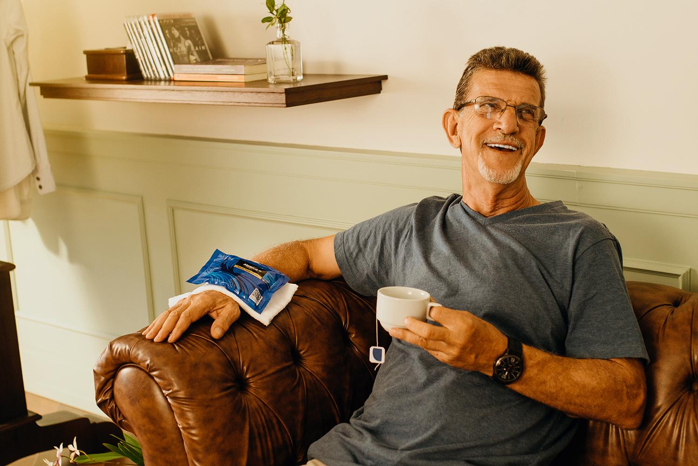 Um homem está sentado em um sofá, sorrindo. Seu braço direito está apoiado e sobre o sofá usando uma bolsa térmica gel. Com o outro braço ele segura uma xícara com chá.