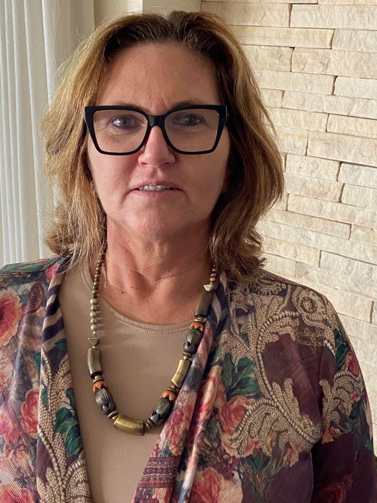 Uma mulher está posando para foto. Ela utiliza óculos de grau, colar com pedras coloridas, casaco estampado e está em uma sala com tijolos e cortina na cor bege.