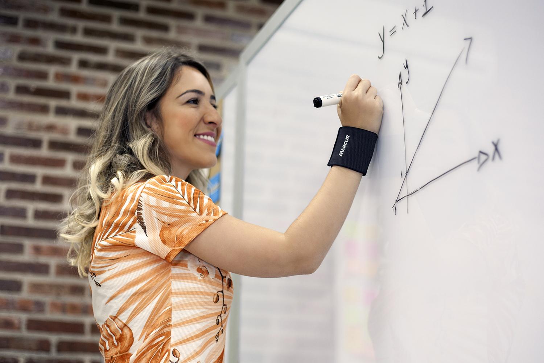 Uma mulher está em frente a um quadro branco, escrevendo com uma caneta. No braço direito ela utiliza uma munhequeira preta.