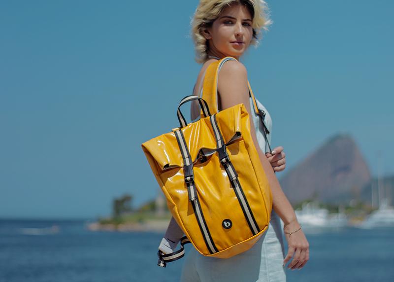 Uma mulher está de pé ao ar livre, em um dia de sol no Rio de Janeiro, utilizando uma mochila amarela.