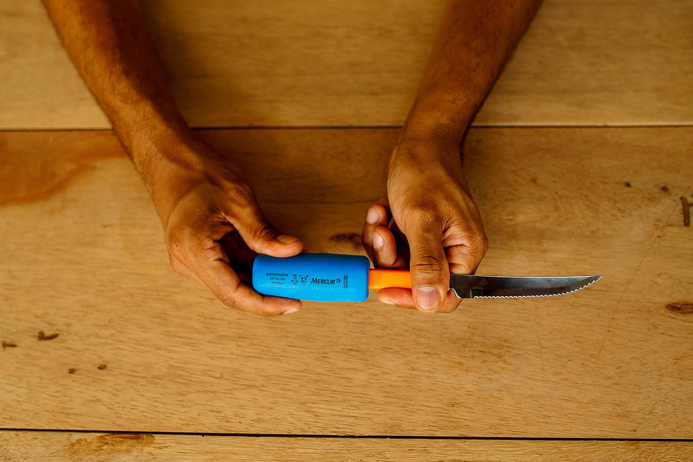 Uma pessoa segura uma faca de metal com cabo de plástico, envolvida pelo Engrossador de Talheres de cor azul.