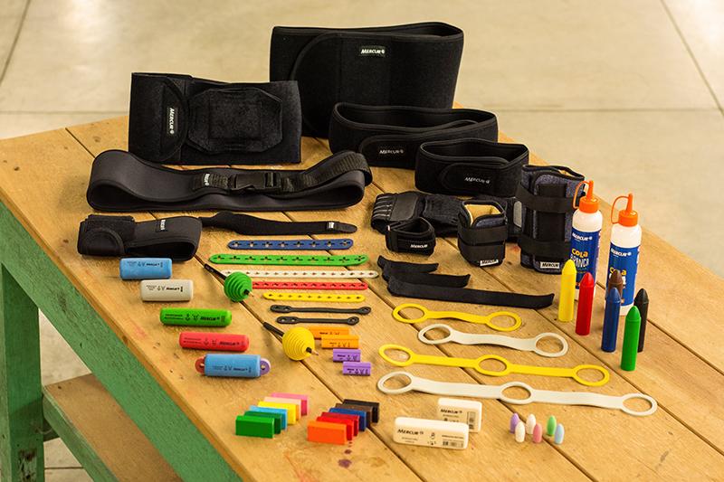 Em uma mesa de madeira, estão dispostos diversos recursos de tecnologia assistiva (como cintas, fixadores, engrossadores) e materiais escolares inclusivos (gizão de cera, cola, borrachas), em diferentes cores.